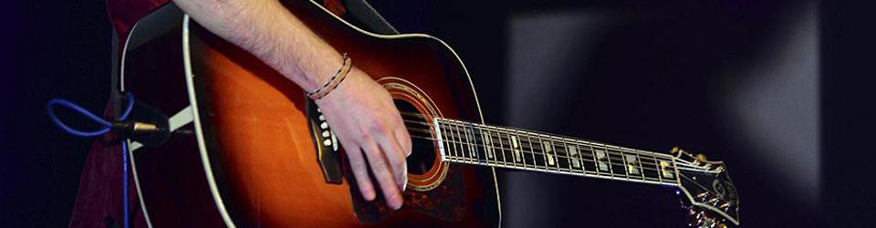 Mano sobre una guitarra