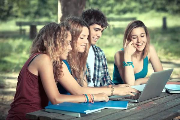 Jóvenes consultando las bases en un portátil